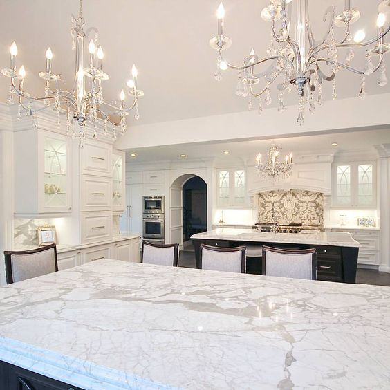 two chic chandleiers with some hanging crystals, marble and lots of white makes the kitchen exquisite