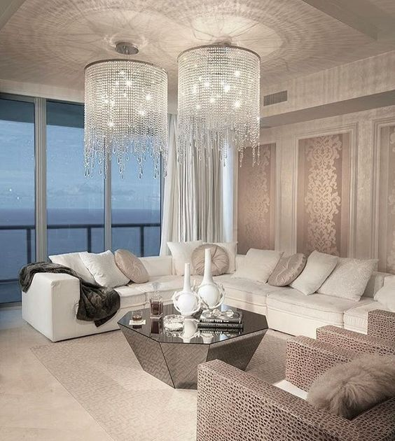 a modern living space with a corner sofa and long crystal chandliers with cascading crystals