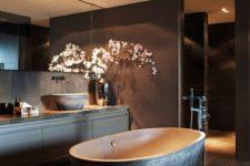 23 a moody bathroom with a dark textural stone bathtub as a focal point