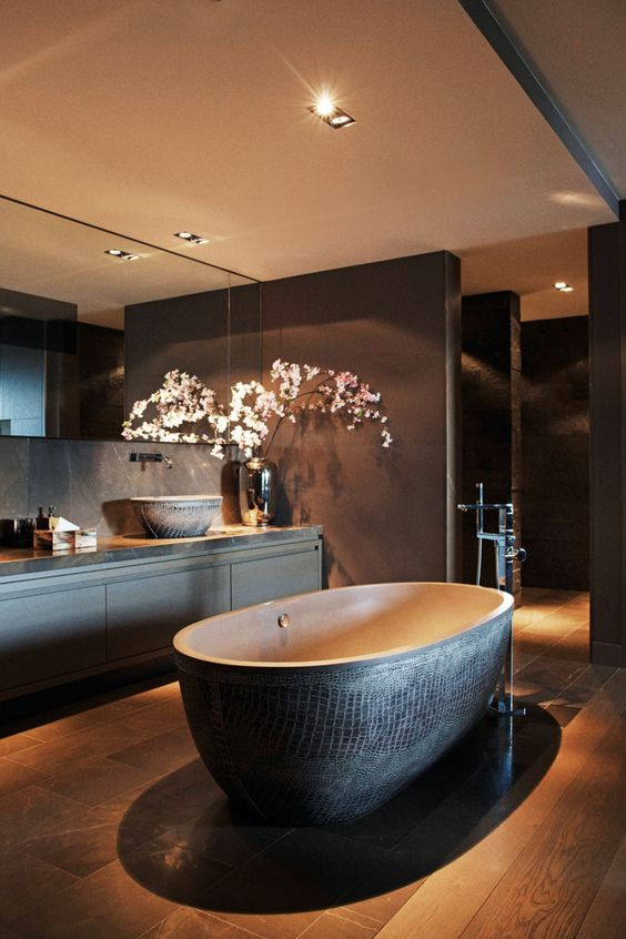 a moody bathroom with a dark textural stone bathtub as a focal point