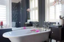 23 a white tub on black claw feet for a modern feminine bathroom