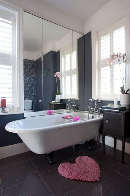 a white tub on black claw feet for a modern feminine bathroom