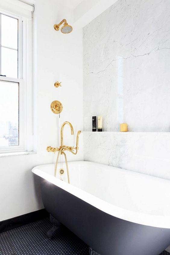 brass fixtures, a black tub and a marble wall to shine