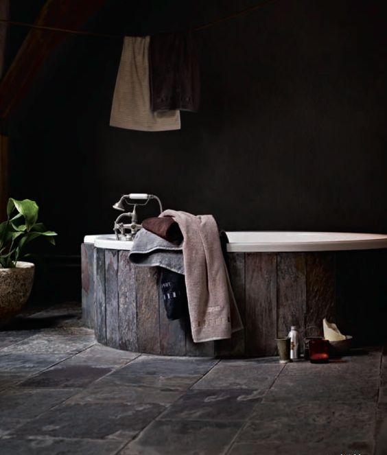 a dark bathroom with a wooden clad bathtub and a stone floor