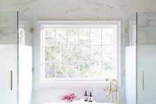 25 chic master bathroom boasts oval freestanding tub and a brass vintage tub filler placed under a window