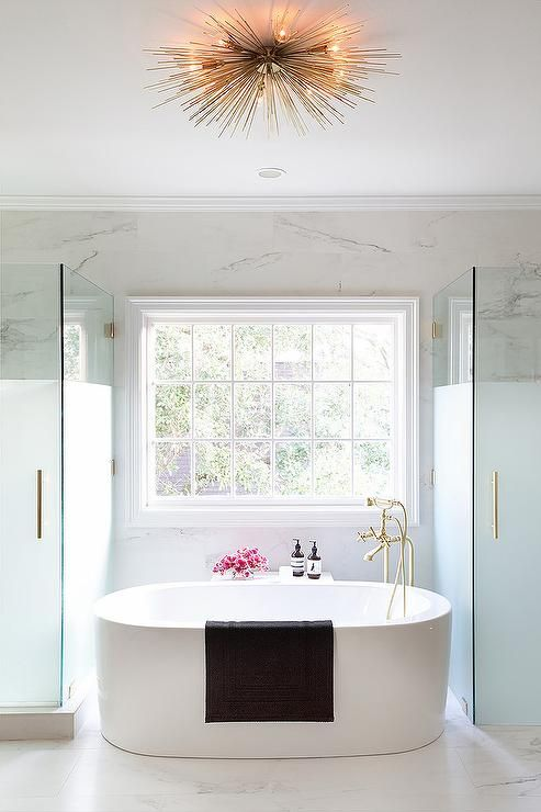 chic master bathroom boasts oval freestanding tub and a brass vintage tub filler placed under a window