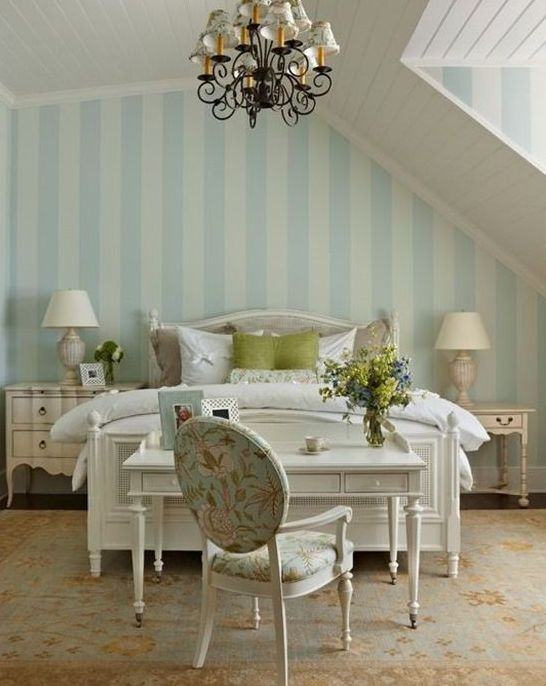 an elegant cottage bedroom with a shabby nightstand and a whitewashed sideboard