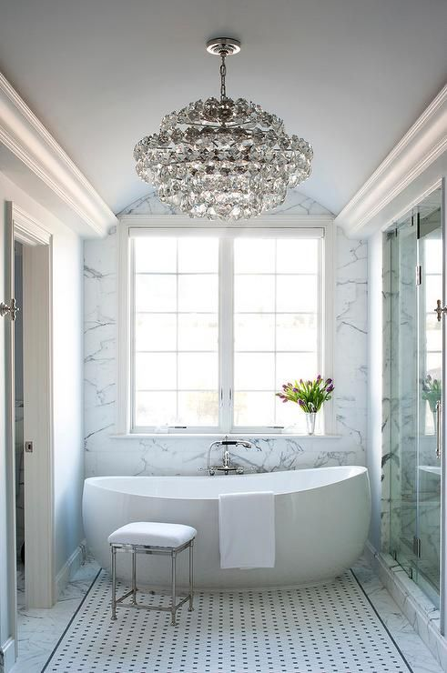 an oversized crystal chandelier in a modern bathroom makes it chic and more girlish
