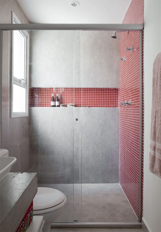 a concrete shower with coral tile inserts looks feminine yet very modern