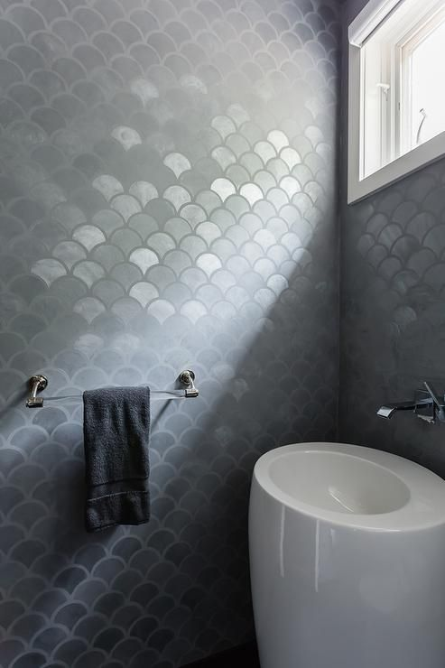a white asymmetrical sink refreshes the moody grey fish scale tiles