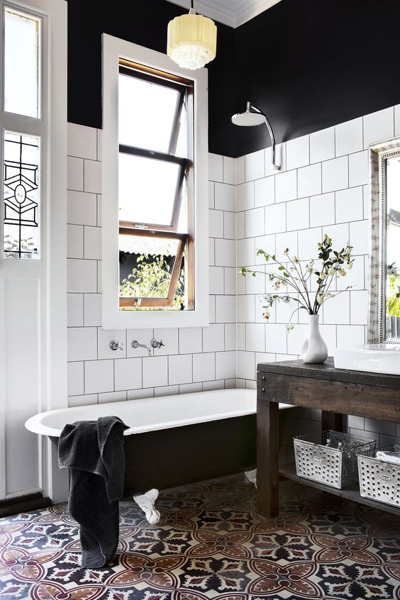 black and white timeless bathtoom with a black tub with white legs looks a bit masculine