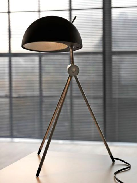 a comfy table lamp on three legs with a black concrete and metal lampshade