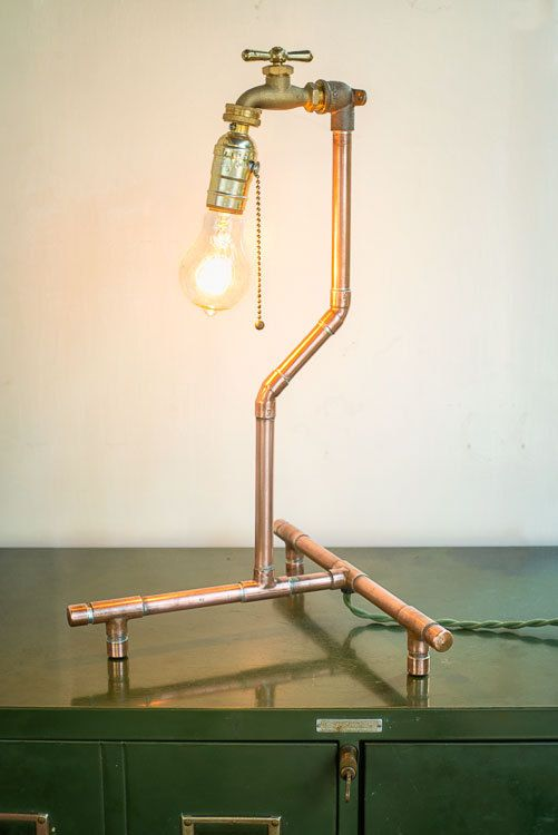 a copper fixture lamp with a bulb and a faucet