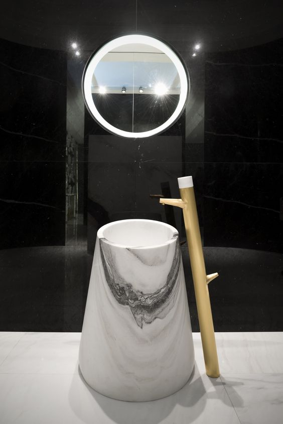 a white marble sink of an eye-catchy shape with a wooden faucet next to it
