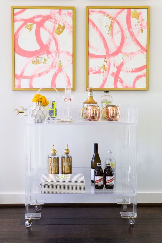 lucite bar cart on casters doesn't steal attention from the wall arts