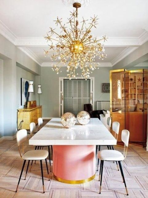 modern girlish dining space with a large gold glam chandelier with stylized flowers and crystals