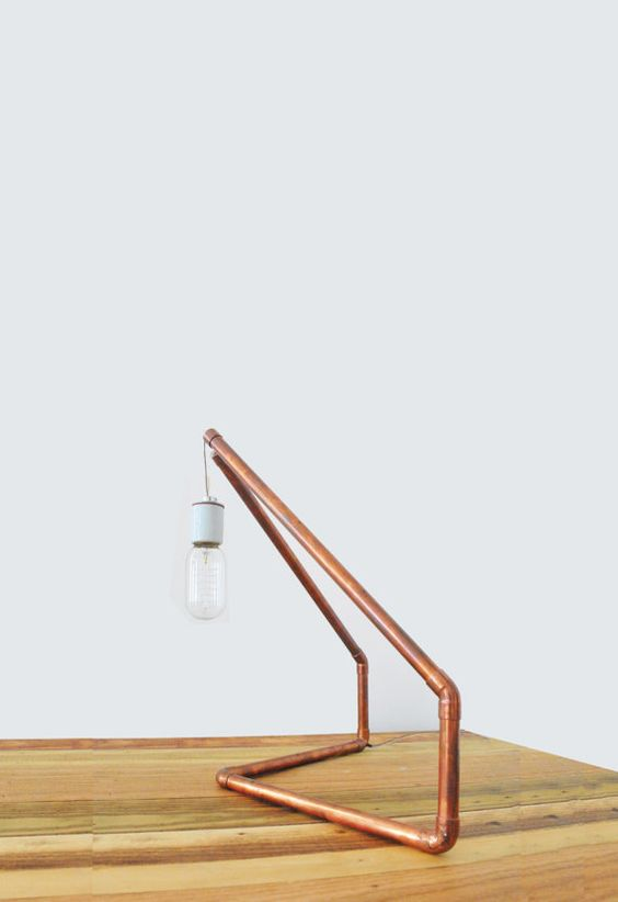 a simple copper pipe geometric lamp with a bulb