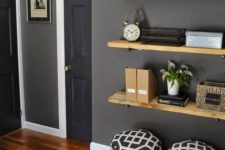 30 light-colored wood floating shelves in front of a grey graphite wall