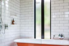 31 a bold orange bathtub in the shower zone with subway tiles