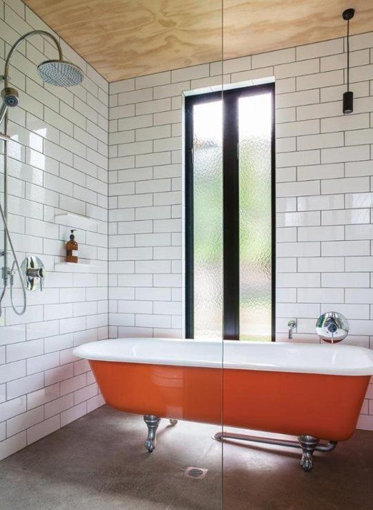 a bold orange bathtub in the shower zone with subway tiles