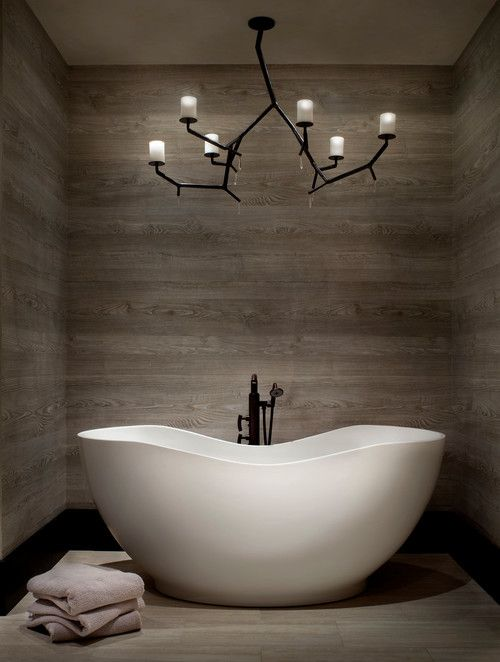 a wood clad bathroom with an eye-catchy tub and a gorgeous chandelier