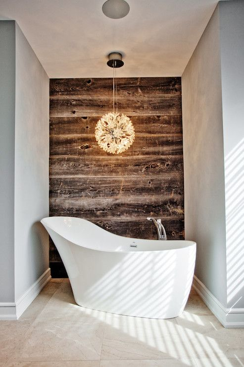 a niche with a reclaimed wall, a glam pendant lamp and a shoes-shaped tub