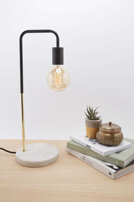 an industrial lamp with a marble base, a brass touch and black elements and a bulb