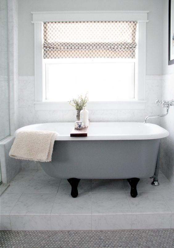 a grey clawfoot bathtub with black legs looks pretty modern