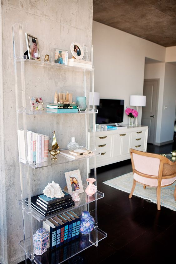ladder-style lucite shelving unit disappears next to the concrete wall