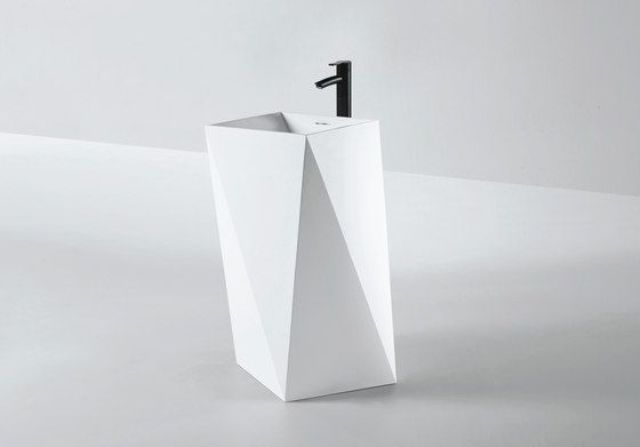 white sculptural faceted sink with a black faucet for a modern bathroom