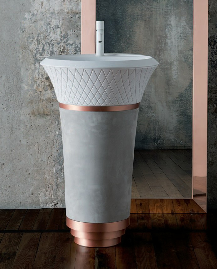 a concrete and copper free-standing sink with a pattern looks eye-catchy
