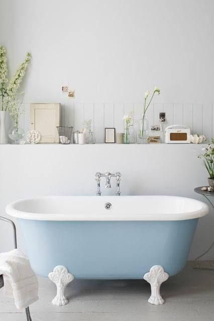 a neutral bathroom with a built-in shelf is complemented with a powder blue clawfoot tub