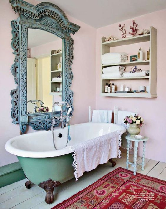 a shabby chic bathroom with a green bathtub on dark metal legs