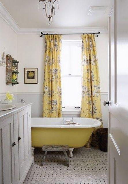 a sunny yellow bathtub and floral curtains for a shiny bathroom