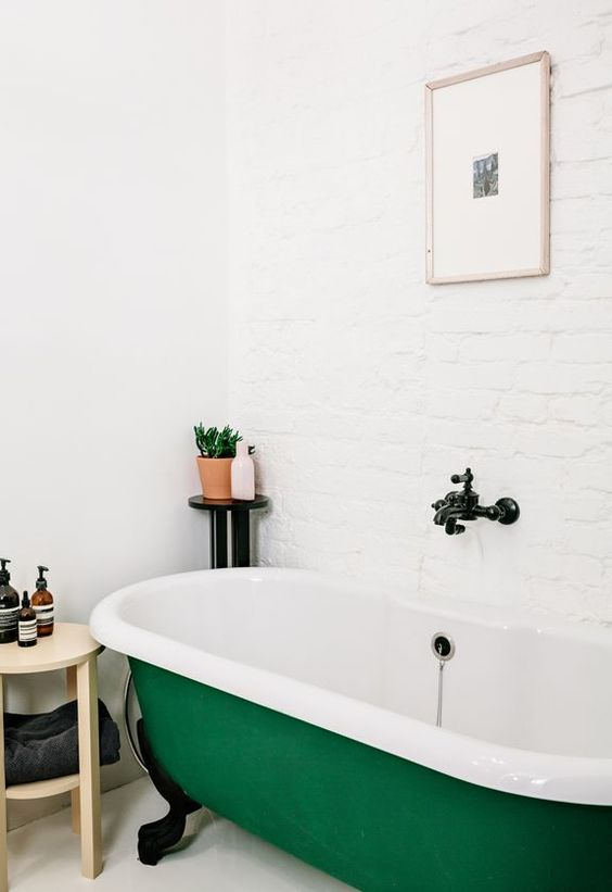 an emerald clawfoot tub is the focal point of this cool space