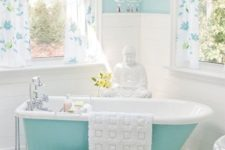 40 aqua-colored clawfoot tub in a girlish bathroom with a chandelier and floral curtains