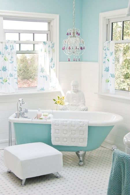 aqua-colored clawfoot tub in a girlish bathroom with a chandelier and floral curtains