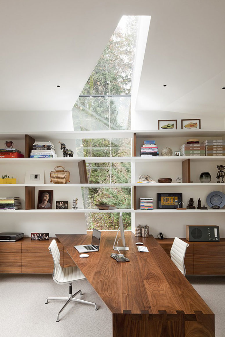 This modern house is strongly connected to the outdoors with glazings, cutouts and skylights
