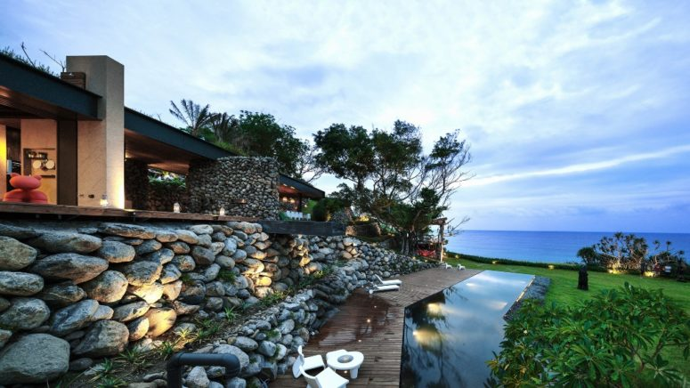 This stunning house is covered with stone that was excavated from its site and it faces the Pacific Ocean
