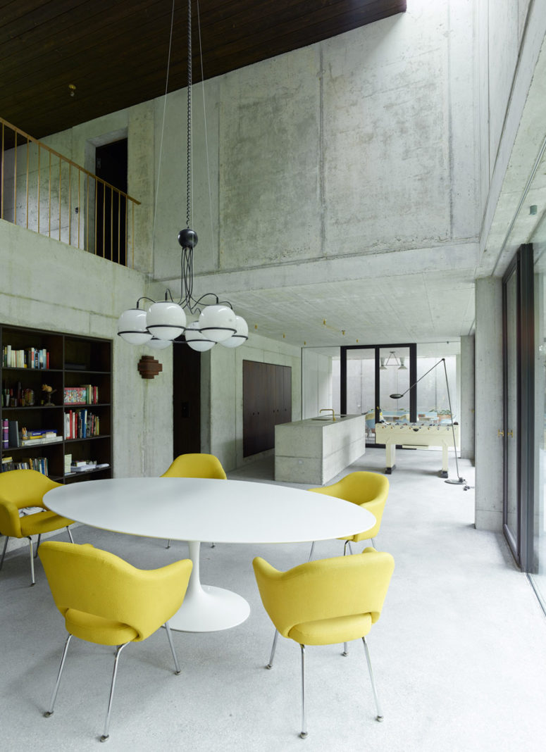 The dining space is modern and vibrant, with sunny yellow chairs and built-in bookshelves
