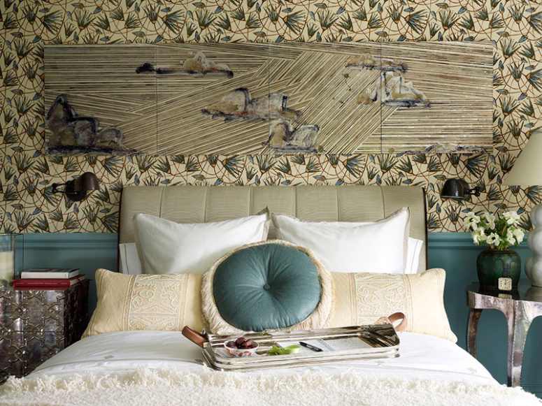 The graphic floral wallpaper coveres the walls and there's wainscoting in the same blue shade