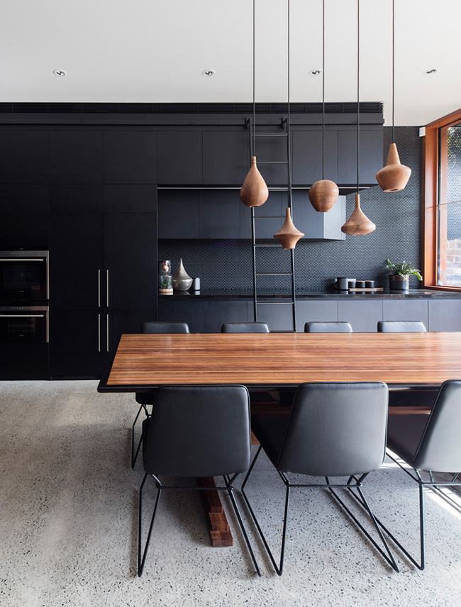 The kitchen features black cabinets, a black penny tile backsplash and a gorgeous wooden dining table with echoing pendants over it