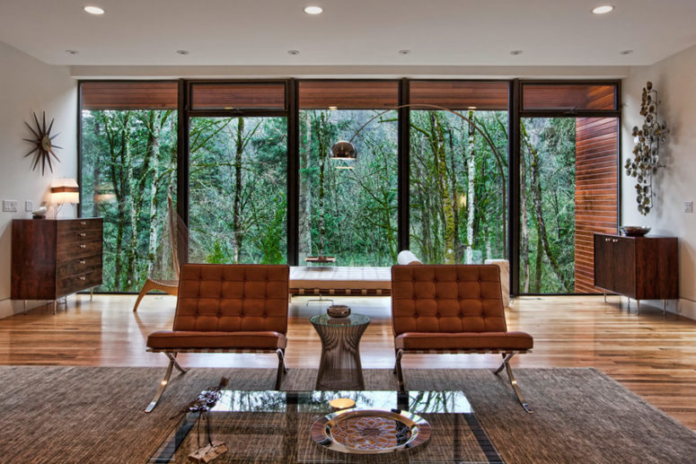 This living space is opened to outdoors with a glazed wall, the furniture is a mix of modern and mid-century modern styles