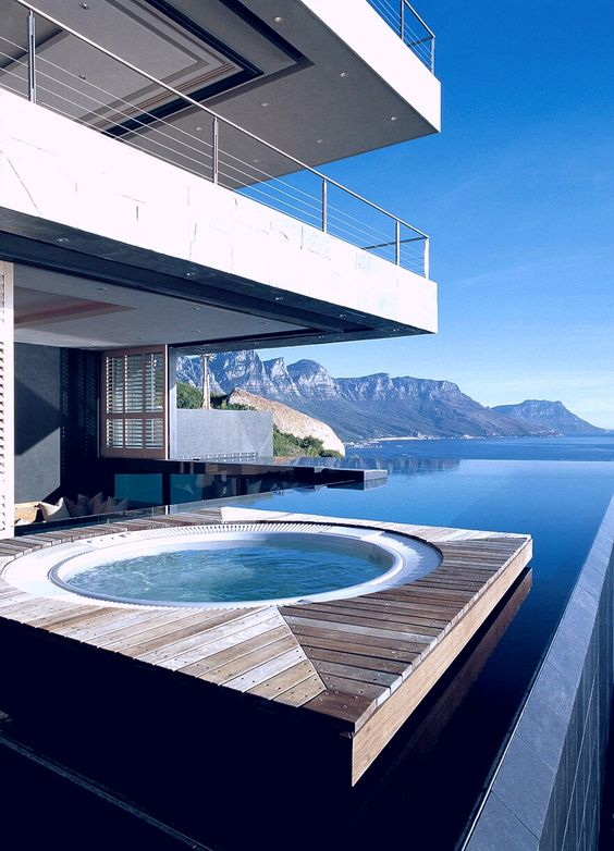 a floating wooden deck in the water with a jacuzzi, a stunning view