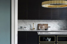 03 The kitchen is very refined, with dark stained cabinets, brass chandeliers and gilded frame kitchen island