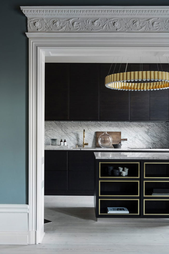 The kitchen is very refined, with dark stained cabinets, brass chandeliers and gilded frame kitchen island