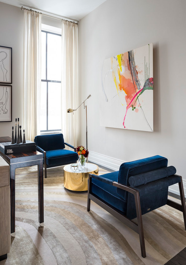 There's a bold abstract artwork on one of the walls and a couple of navy velvet chairs to enjoy it