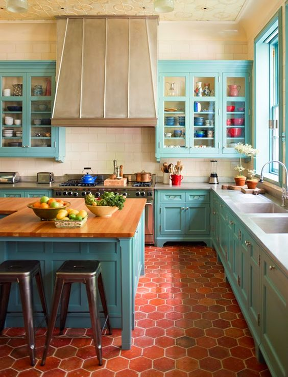bold turquoise kitchen cabinets contrast with red tiles on the floor