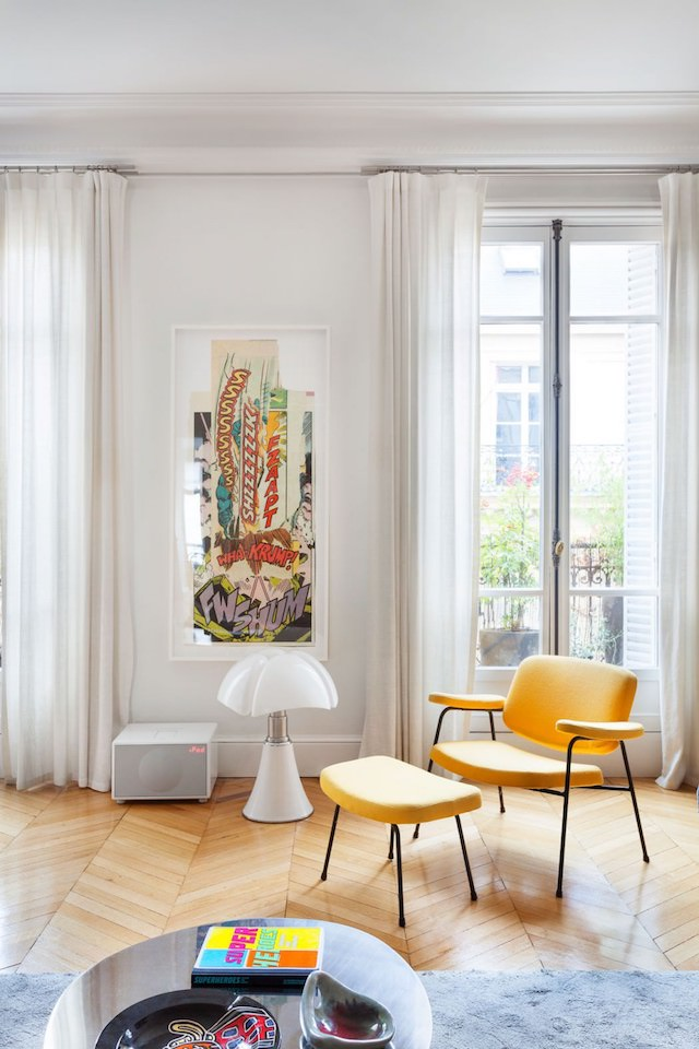 A comfy reading nook by the window with a sunny yellow chair with a footrest and a vintage poster