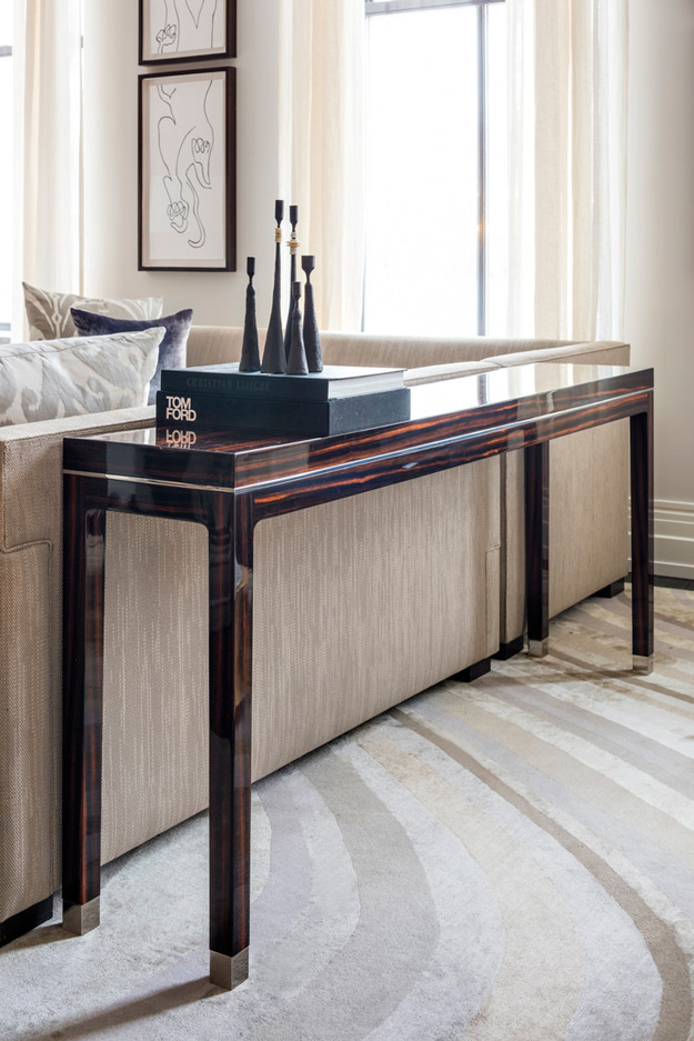 The console table is of dark stained and polished wood, and it adds elegance